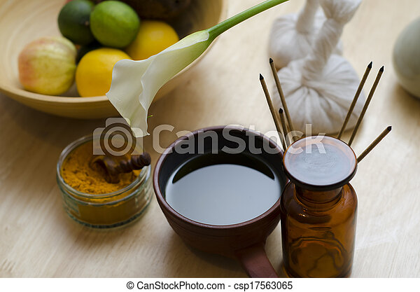 A countertop arrangement of ayurvedic turmeric spice, oil and massaging tools and an exotic flower used in Ayurveda massage. - csp17563065