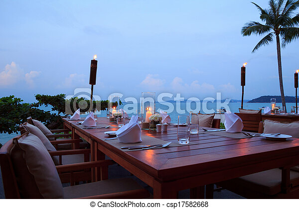 Romantic dinner setting at the beach on sunset, outdoor restaurant tables - csp17582668