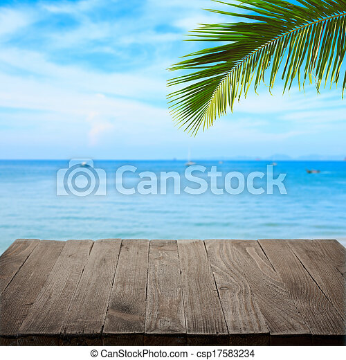 Empty wooden table with tropical sea and palm leaf on background, blank place for product - csp17583234