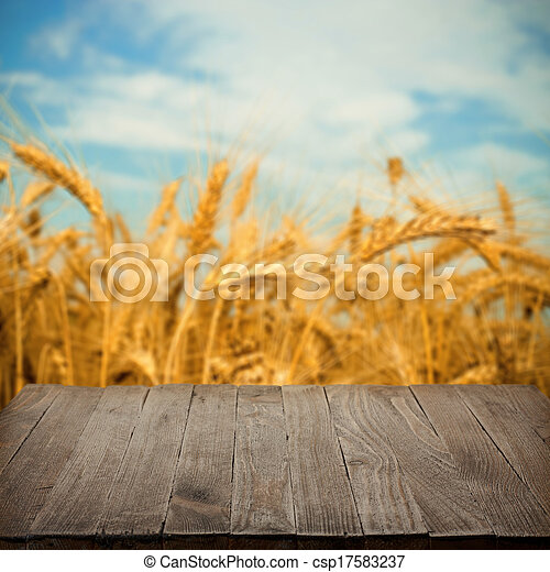 Empty wooden table with wheat field on background, blank place for product - csp17583237