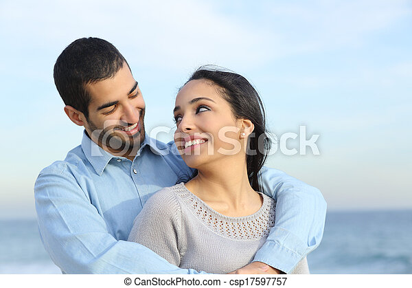 Arab casual couple cuddling happy with love on the beach - csp17597757