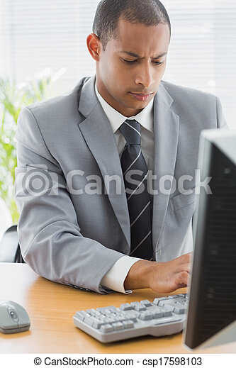 Concentrated businessman using computer at office - csp17598103