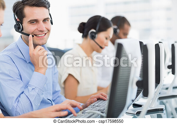 Business colleagues with headsets using computers - csp17598550