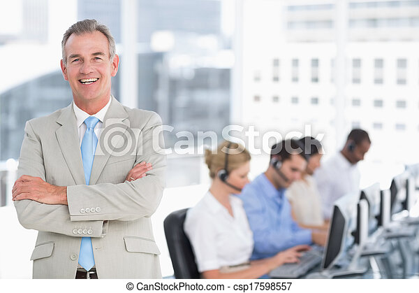 Happy businessman with executives using computers in office - csp17598557