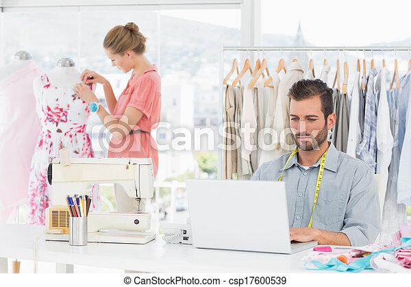 Man using laptop with fashion designer working at studio - csp17600539