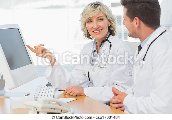 Doctors using computer at medical office - csp17601484