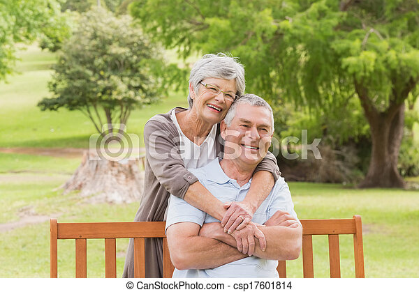 Senior woman embracing man from behind at park - csp17601814