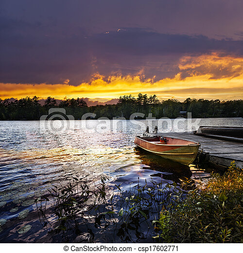 Boat docked on lake at sunset - csp17602771