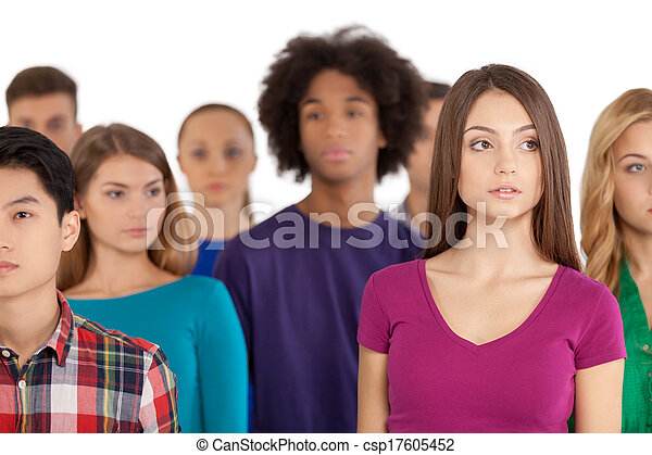 Loneliness in a crowd. Frustrated young woman standing among multi-ethnic group of people and looking away - csp17605452