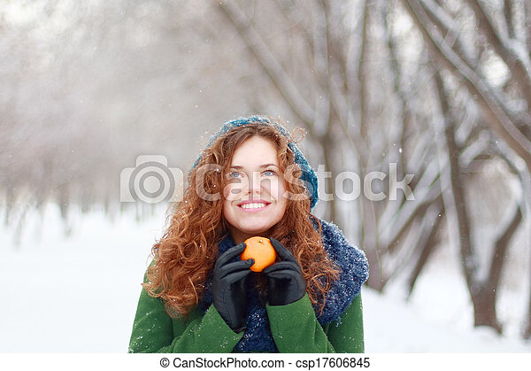 Beautiful girl in blue beret holds mandarin and looks up at winter day in park - csp17606845