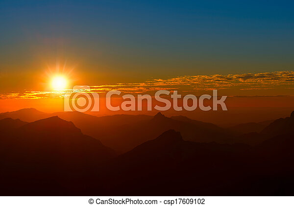 sunset between mountains and clouds with red sky - csp17609102