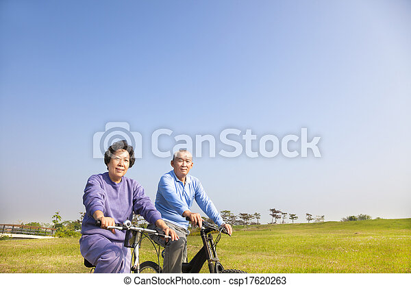 asian seniors couple biking in the park - csp17620263