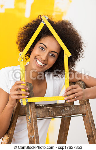 Smiling woman decorating her new house - csp17627353