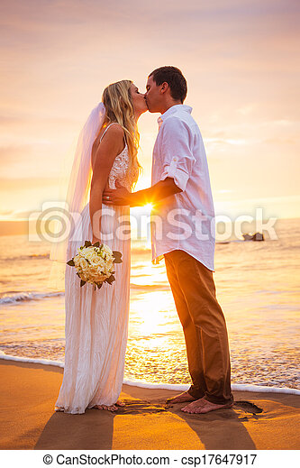 Married couple, bride and groom, kissing at sunset on beautiful tropical beach in Hawaii - csp17647917