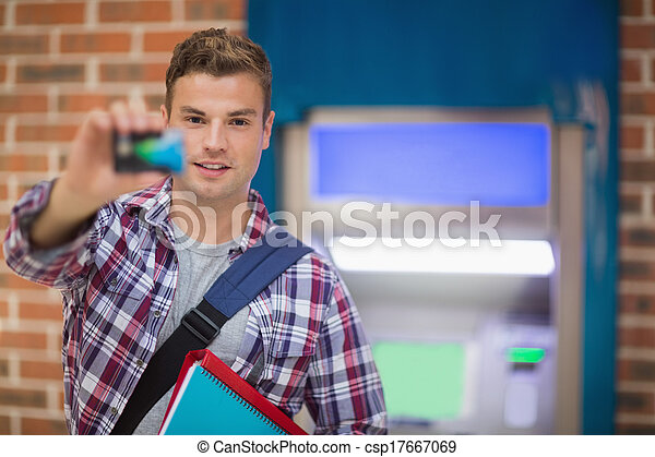 Student showing his card to camera at the ATM
