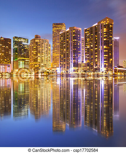 City of Miami Florida, night skyline. Cityscape of residential and business buildings illuminated at sunset with reflection - csp17702584