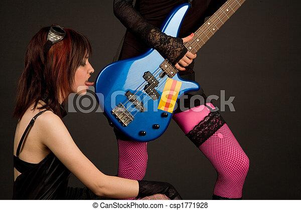 Rock girl licking bass guitar - csp1771928