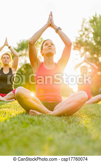 group of 3 women doing yoga in nature - csp17760074