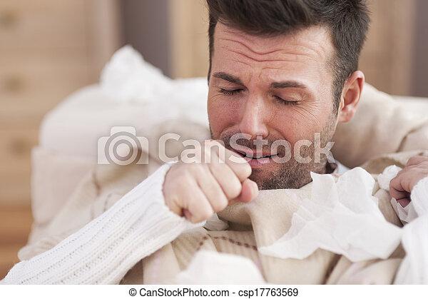 Sick man lying on sofa in living room