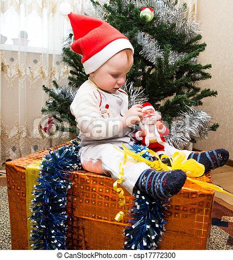 Santa baby boy with gift box near Christmas tree at home