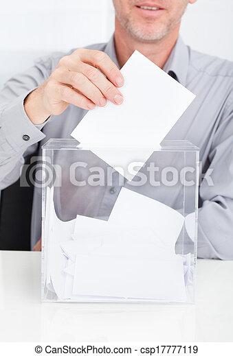 Person Inserting Ballot In Box - csp17777119