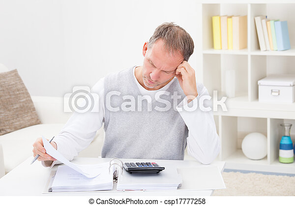 Thoughtful Man Holding Calculator - csp17777258