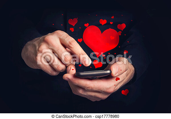 Man typing love text messages on a smartphone for Valentine's day. Selective focus on hands and phone device. - csp17778980