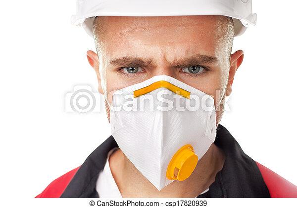 Serious worker wearing respirator - csp17820939