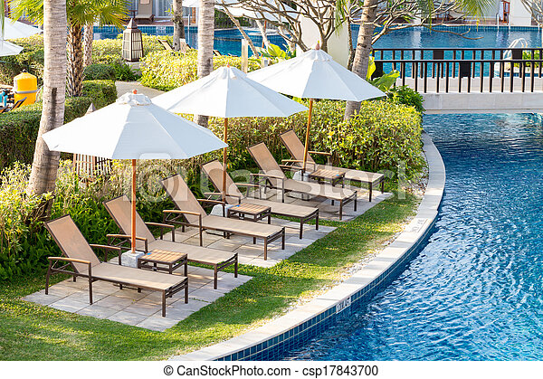 Relaxing chairs beside of swimming pool in residential garden - csp17843700