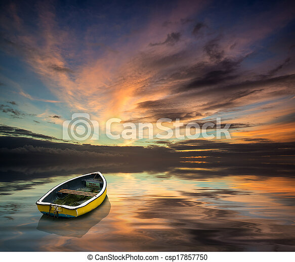 Stunning vibrant blue and pink Winter sky with single boat floating on ocean - csp17857750
