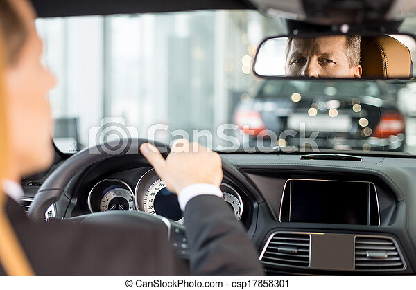 Feeling confident in his new car. Rear view of confident senior man in formalwear sitting on drivers place in car and looking at mirror - csp17858301