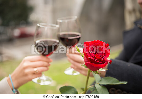 close up a single rose with a coule drinking wine - csp17893159
