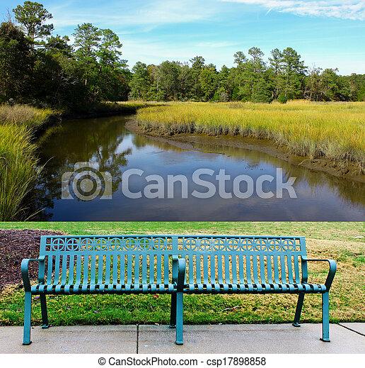 lone single green metal park bench on the sidewalk walkway along the ...