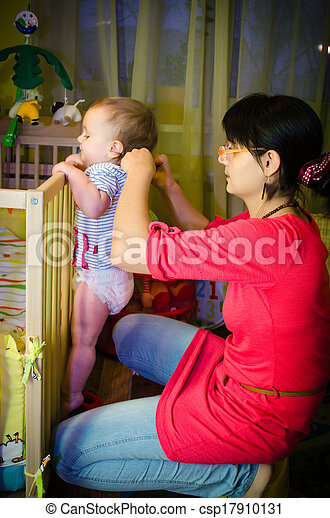 Child in the crib playing with mom