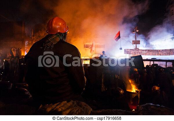 KIEV, UKRAINE - January 24, 2014: Mass anti-government protests in the center of the Ukrainian capital Kiev. Popular Resistance Warrior preparing to storm by government troops  on Hrushevskoho St.   - csp17916658