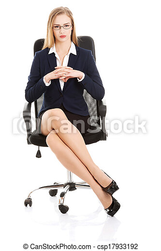 Beautiful young business woman sitting on a chair.