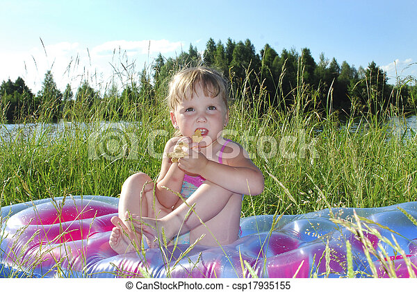 Picnic. Little girl sitting on the grass near the lake - csp17935155