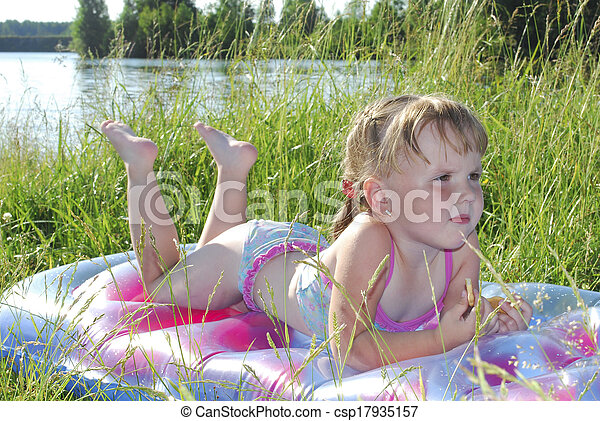 Summer little girl sunning at the lake in the grass - csp17935157
