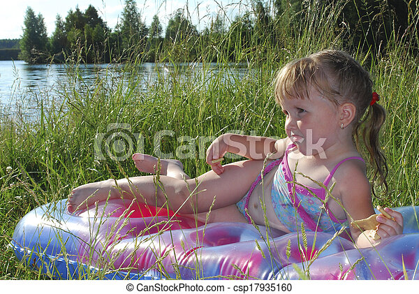 Summer little girl sunning at the lake in the grass - csp17935160