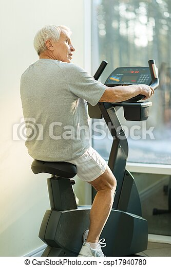 Senior man doing exercise on a bike in a fitness club - csp17940780