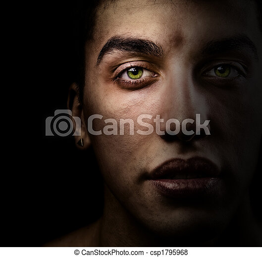 Face of beautiful man with green eyes in the shadow - csp1795968
