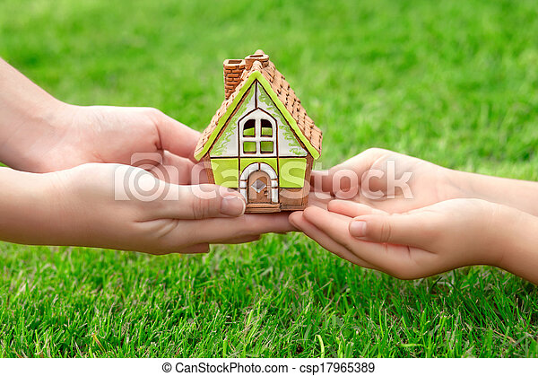 Hands mother and a small child holding a little toy house on a background of green grass - csp17965389