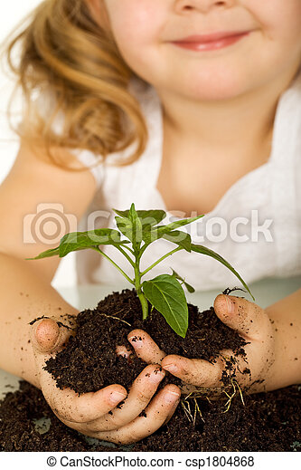 Little girl holding a young plant in soil - closeup - csp1804868