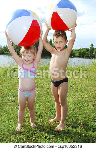 the lake a little boy and girl playing with an inflatable ball - csp18052316