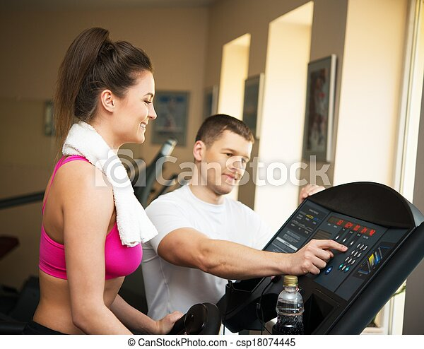 Trainer explains to a young woman how to use treadmill in fitness club - csp18074445