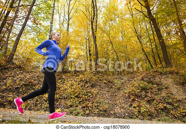 Active and sporty woman runner in autumn nature - csp18078900