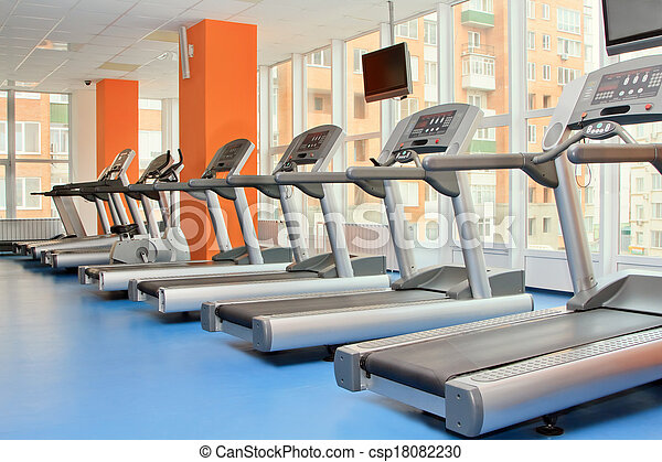 Gym with windows and running machines in fitness center - csp18082230