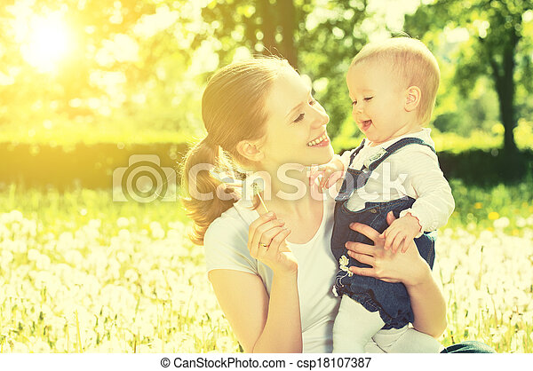 Beautiful happy little baby girl in a wreath  on a  meadow with yellow flowers dandelions on the nature in the park - csp18107387
