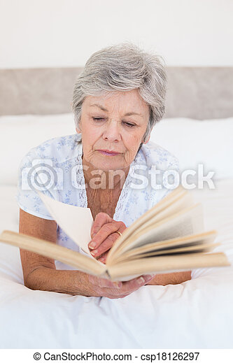 Senior woman reading story book in bed - csp18126297
