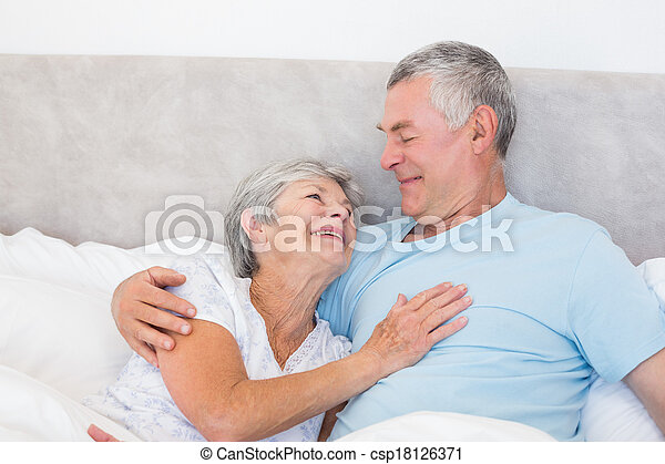 Senior man looking at wife in bed
